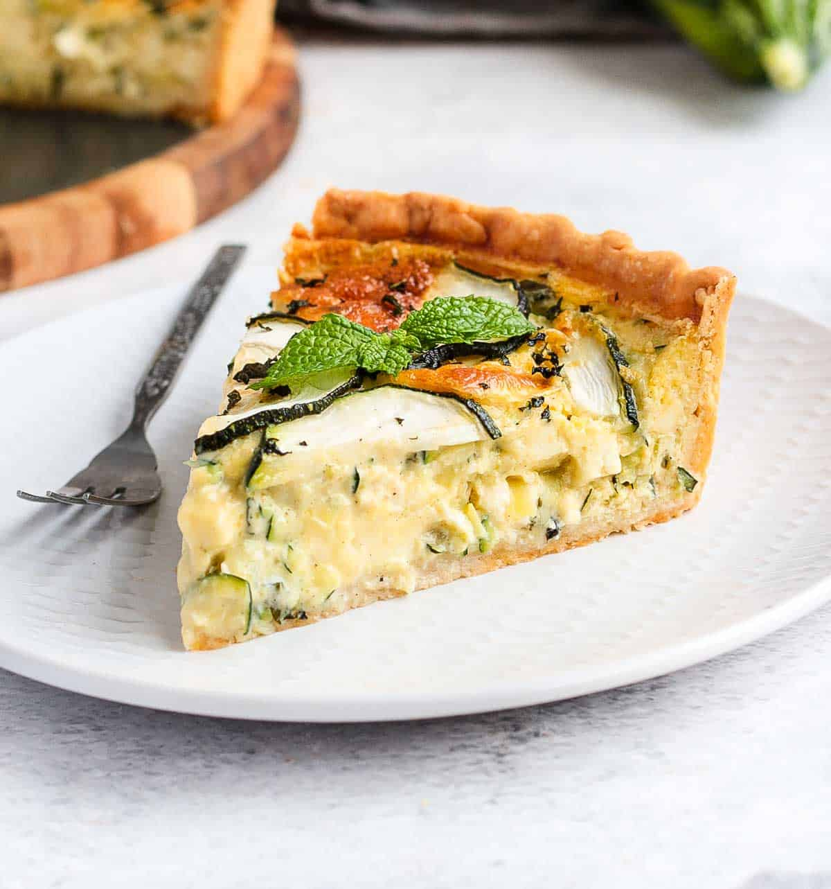 One slice of quiche on a white plate.