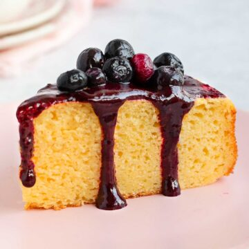 A slice of cake drizzled with the blueberry sauce.