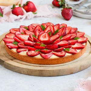 Close up on the strawberry tart placed over a wooden round board.