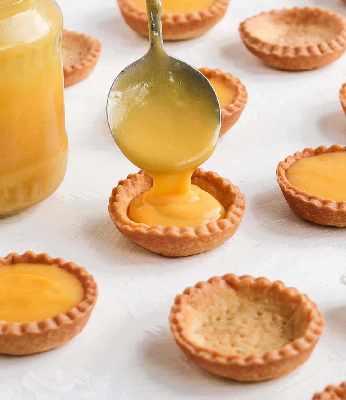 Pouring orange curd inside a tartlet shell,
