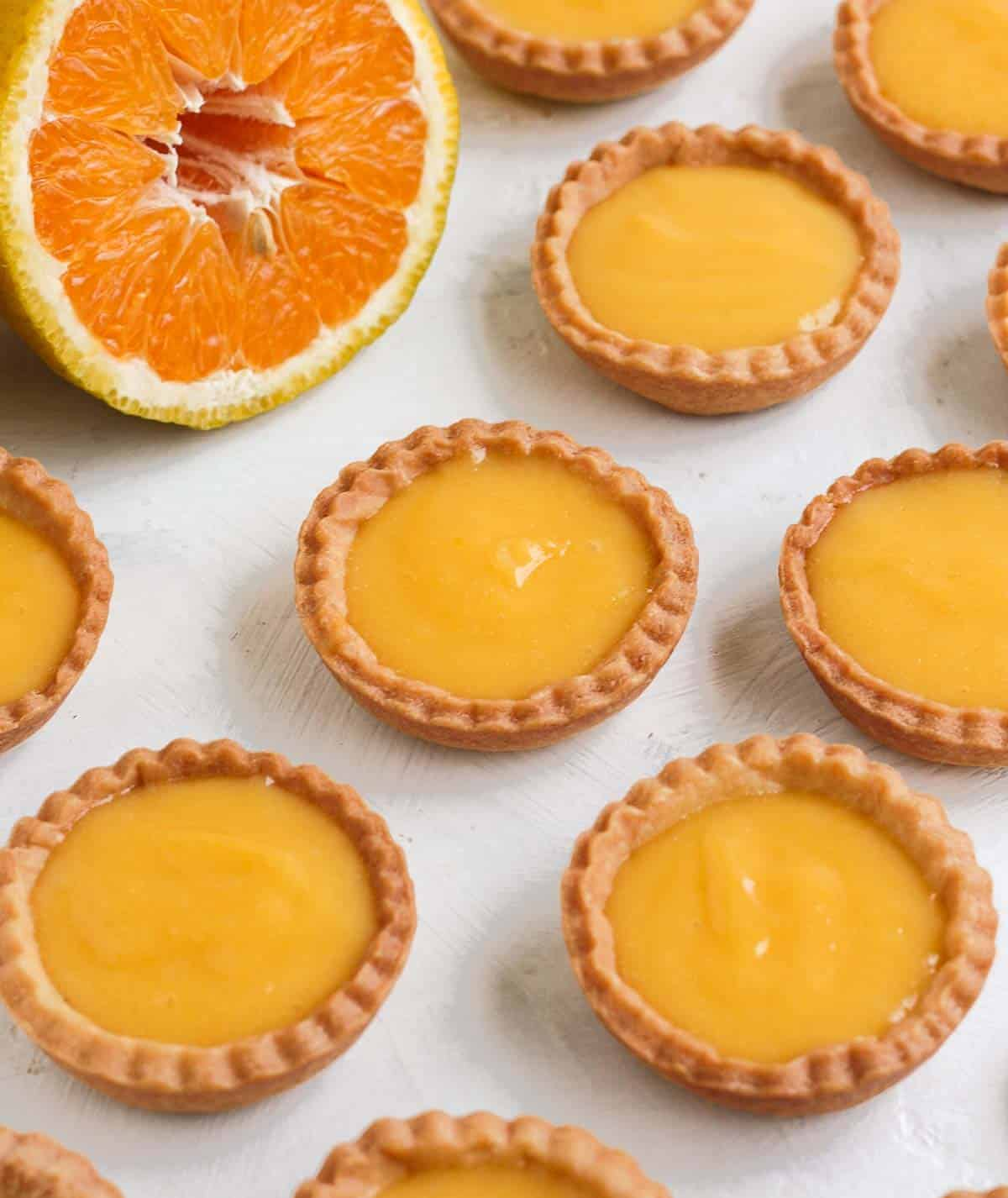 Tartlets on a white surface with half an orange in the background.
