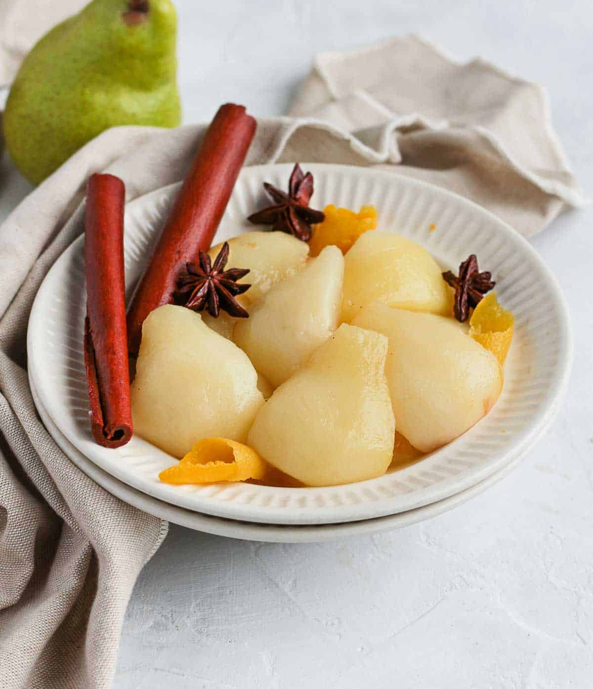 Cooked pears in a white bowl with beige napkin.