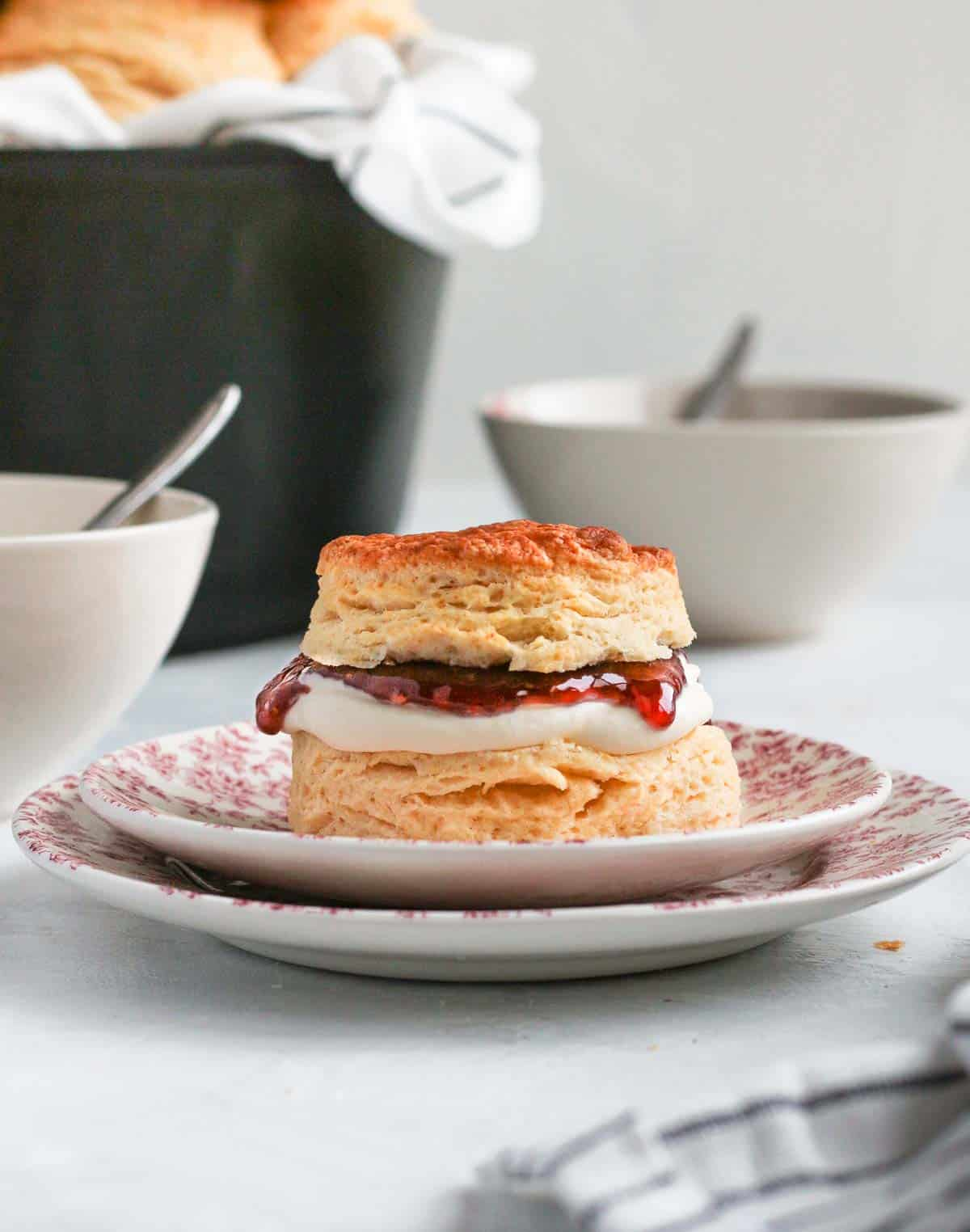 One scone filled with cream and jam on two pink plates.
