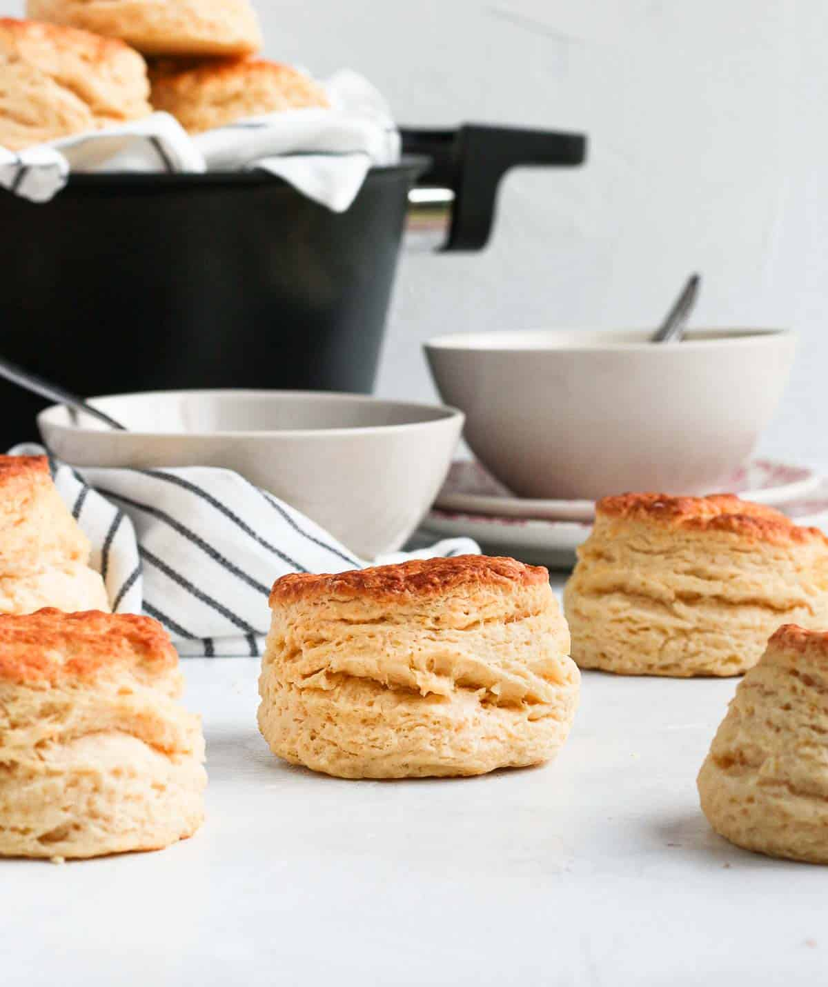 Scones on a white surface with two white bowls and the remoska in the background.