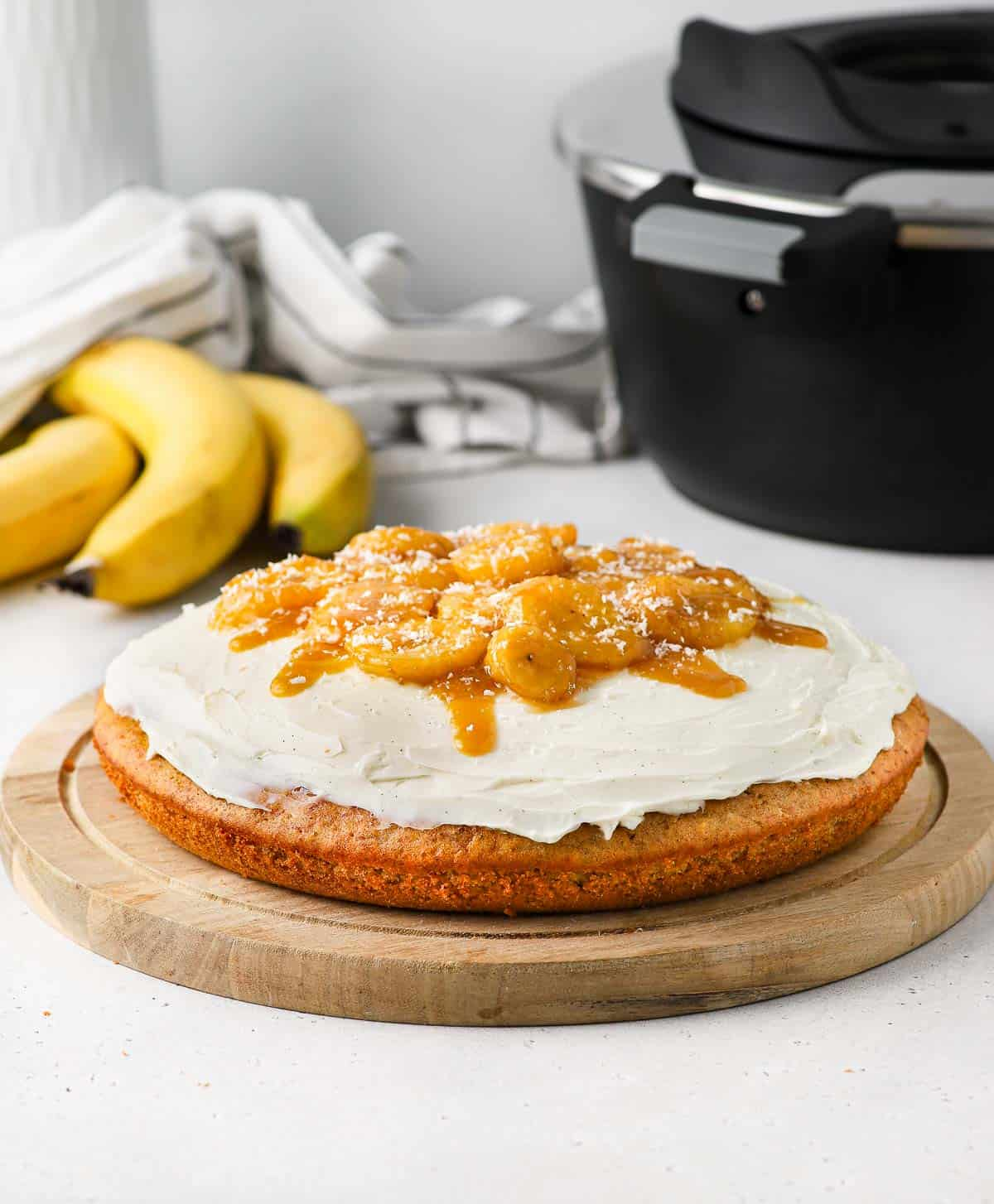 Banana Cake on a wooden board with the Remoska in the background.