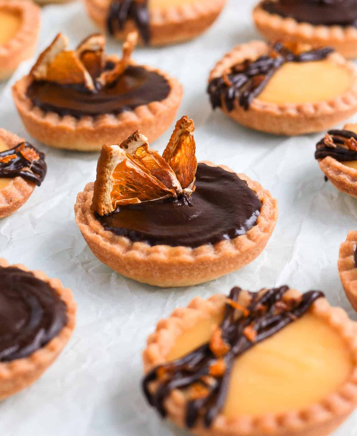 Close up on one tartlet topped with dried oranges.