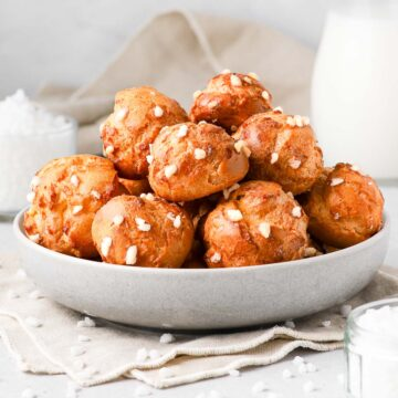 Chouquettes stacked in a grey bowl.