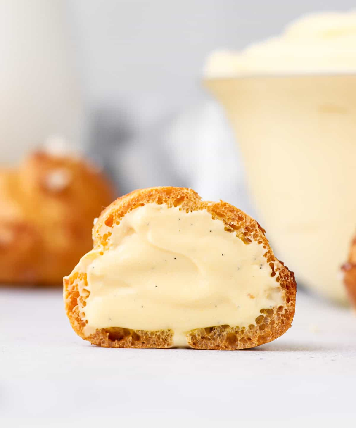 Choux bun cut in half filled with cream.